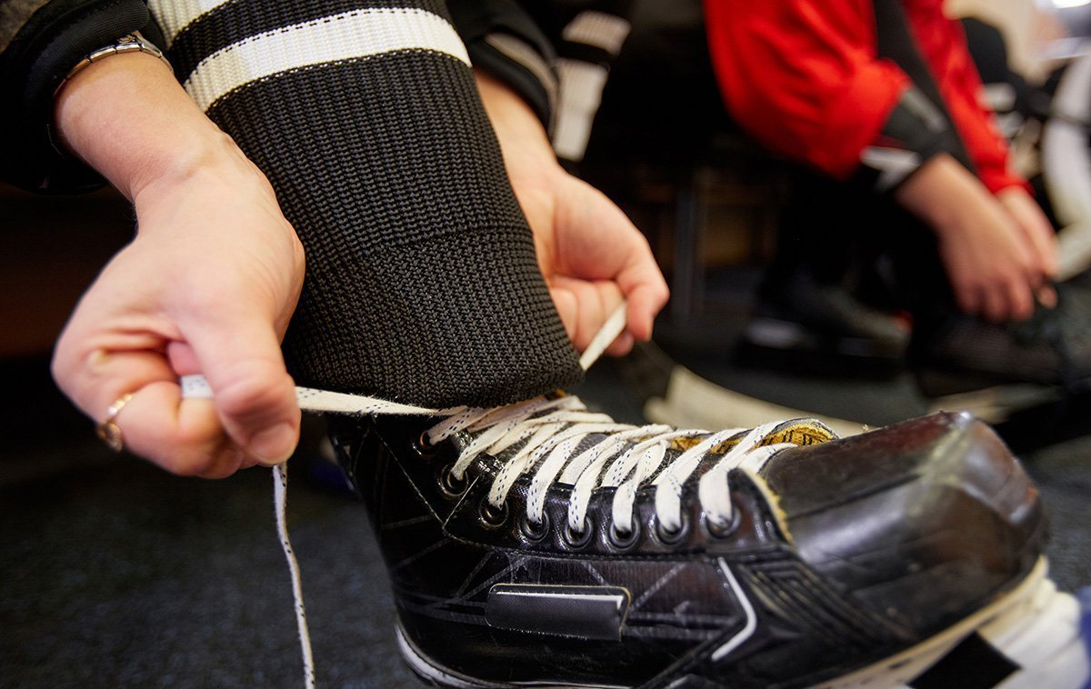 Close Up Of A Hockey Player Putting On Gear In Locker Room With Rubber Flooring